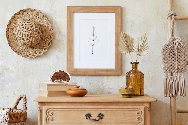 Stilvolles boho-interieur des wohnzimmers mit braunem plakatrahmen, eleganten accessoires, blumen in der vase, holzregal und hängender rattanhütte
