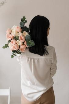 Stilvolles brünettes mädchen in einem weißen hemd mit einem blumenstrauß auf ihrer schulter