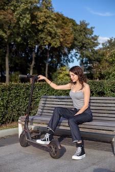 Stilvolles brunettemädchen, das draußen auf einer bank mit ihrem escooter in einem park bei sonnigem wetter sitzt