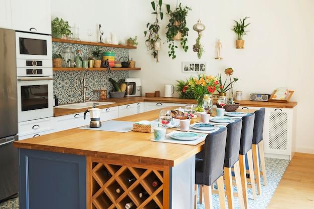 Stilvolles design des kücheninnenraums mit esstisch, stühlen, geschirr und anderem küchenzubehör. mediterraner stil. heller und sonniger platz. helle farben. sommergefühl.