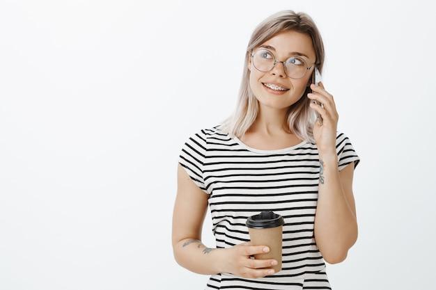 Stilvolles entspanntes blondes mädchen, das im studio mit ihrem telefon und kaffee aufwirft