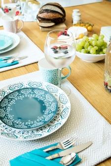 Stilvolles esszimmer-innendesign mit tellern, tassen, gläsern und speisen im mediterranen stil
