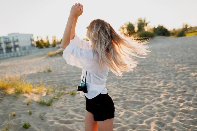 Stilvolles formschönes mädchen mit retro-kamera, die am sonnigen abendstrand aufwirft. sommerurlaub. tropische stimmung. freiheits- und reisekonzept.