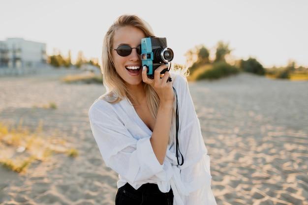 Stilvolles formschönes mädchen mit retro-kamera, die auf sonnigem strand aufwirft. sommerurlaub. tropische stimmung. freiheits- und reisekonzept.