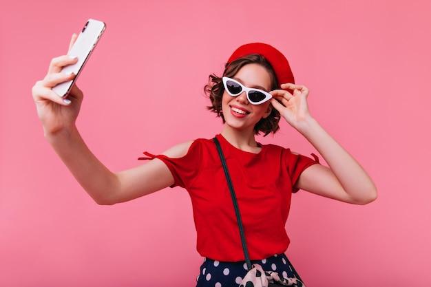 Stilvolles französisches mädchen mit tätowierungen, die selfie machen. elegante weiße frau in baskenmütze und sonnenbrille, die foto von sich selbst machen.