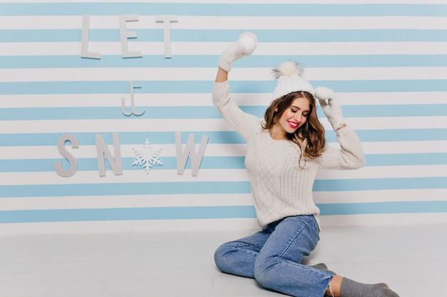 Stilvolles frauenmodell, das warmen pullover und lustigen hut trägt und mit schneeweißem ball in ihrer hand aufwirft