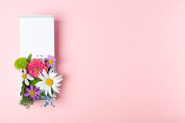 Stilvolles frisches blumenarrangement in weißer geschenkbox auf rosa hintergrund