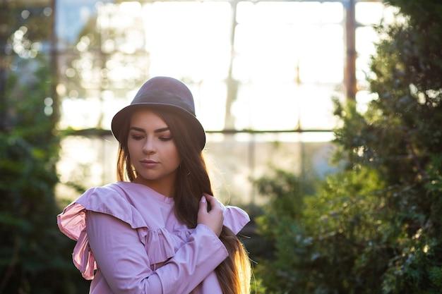 Stilvolles gebräuntes mädchen mit trendiger bluse und hut, das im freien mit sonnenlicht posiert. freiraum