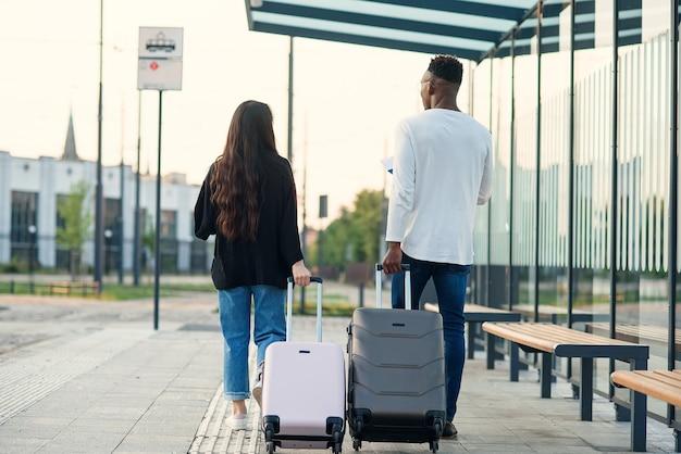 Stilvolles gemischtrassiges paar, das seine koffer auf rädern trägt, die zur flughafenrichtung gehen.