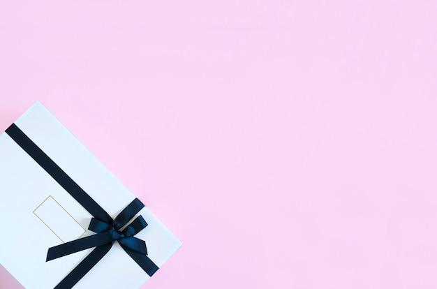 Stilvolles geschenk für frau, dame - weißer kasten mit schwarzem farbband auf rosafarbenem hintergrund mit exemplarplatz für text. überraschung für den urlaub, valentinstag, 8. märz, geburtstag, hochzeit