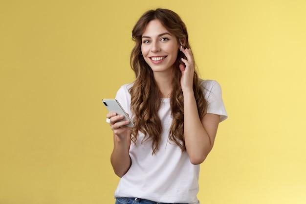 Stilvolles, gut aussehendes, sorgloses urbanes mädchen, das kopfhörer aufsetzt, musik hört, drahtlose ohrhörer-touch-kopfhörer, lächelnd, erfreut, kamera, tolles neues track-hold-smartphone gefunden, musik hören