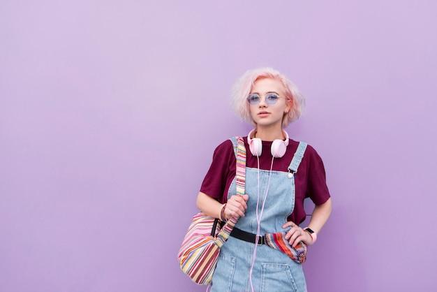 Stilvolles helles junges mädchen mit kopfhörersonnenbrille und gefärbtem haar auf einem lila hintergrund