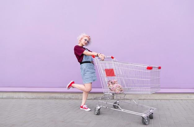 Stilvolles helles mädchen mit gefärbten haaren wirft mit einem einkaufswagen auf einem lila hintergrund auf