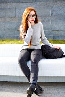Stilvolles herbst-winter-porträt im freien von hübschem ingwer-teenie-mädchen, stilvolles schickes lässiges outfit und rucksack, klare sonnenbrille