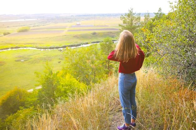 Stilvolles hippie-mädchen, das auf dem berghügel steht. glückliche frau, die die herbstnatur genießt. schöne landschaft. lifestyle-reisekonzept. dunkelroter pullover. gelbe blätter an bäumen.
