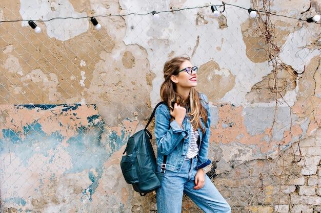 Stilvolles hipster-mädchen im retro-jeansanzug, der vor der alten mauer aufwirft. trendy junge frau mit tasche, die neben altem gebäude steht.