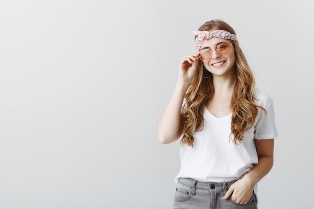 Stilvolles hipster-mädchen in der sonnenbrille, die glücklich lächelt