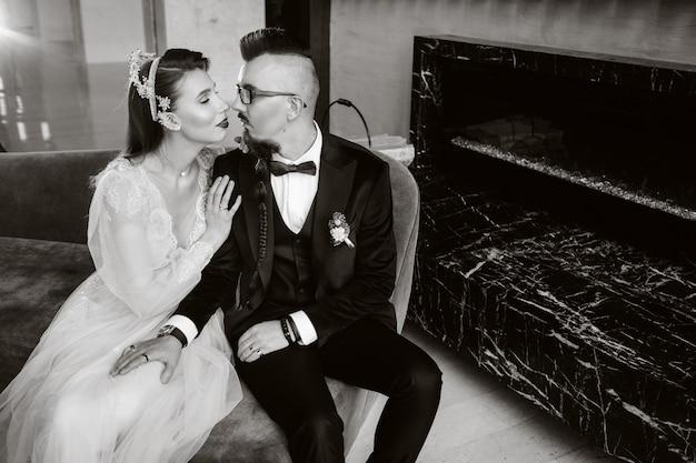 Stilvolles hochzeitspaar im innenraum. glamouröse braut und bräutigam, schwarzweiss-foto