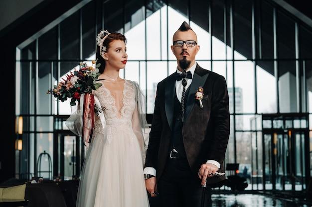 Stilvolles hochzeitspaar im innenraum. glamouröse braut und bräutigam.