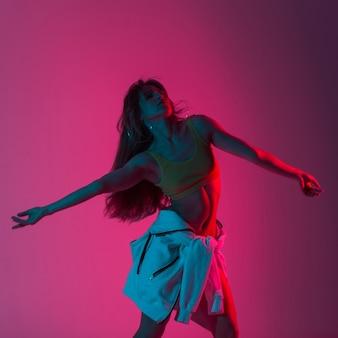 Stilvolles hübsches junges frauenmodell in sportkleidung genießt einen tanz in einem raum mit mehrfarbigem flackern. schönes sexy mädchen, das drinnen mit leuchtend rosa neonlicht tanzt.