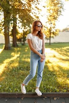 Stilvolles hübsches mädchen im weißen t-shirt der hoch taillierten jeans und in den turnschuhen in einem park auf einem der bäume bei sonnenuntergang