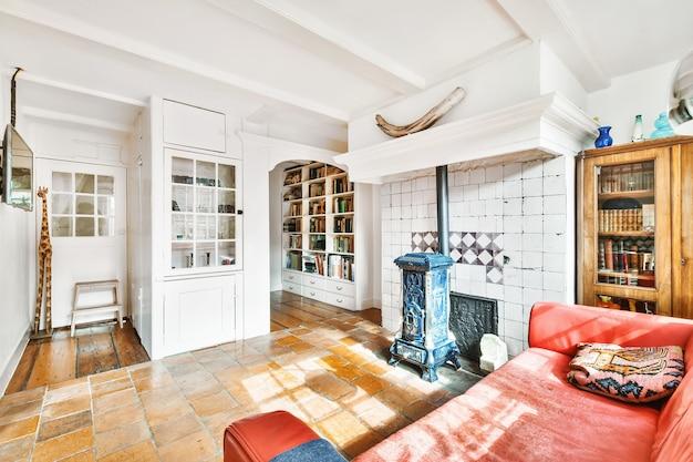 Stilvolles innendesign des wohnzimmers mit hellen möbeln und weicher, bequemer couch und teppich sowie mit fernseher am schrank in einer modernen wohnung mit offener küche und weißen wänden und säulen.