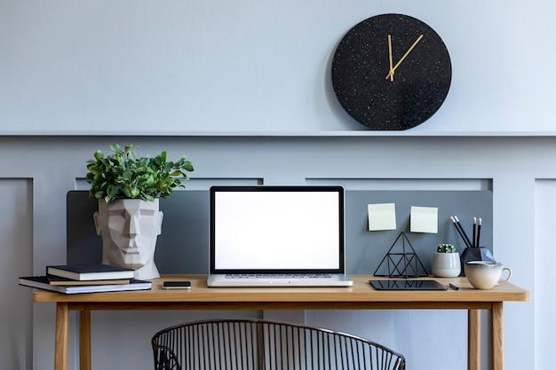 Stilvolles interieur des home-office-raums mit laptop-bildschirm, holzschreibtisch, pflanze, büchern, notizen, stuhl, holzvertäfelung und elegantem bürozubehör in der designwohnung.