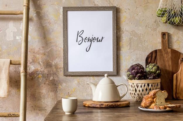 Stilvolles interieur des küchenraums mit holztisch, braunem fotorahmen, kräutern, gemüse, teekanne, tassen und küchenzubehör im wabi-sabi-konzept der wohnkultur.