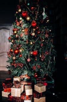 Stilvolles interieur des raumes mit schönem weihnachtstannenbaum und dekorativem kamin