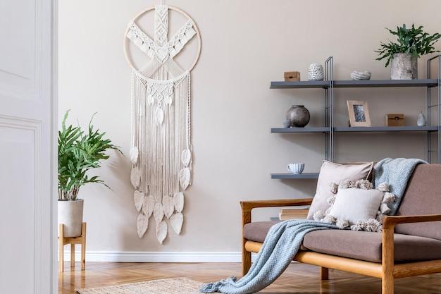 Stilvolles interieur des wohnzimmers in einer gemütlichen wohnung mit braunem sofa, couchtisch, buchständer, vielen pflanzen, makramee und eleganten accessoires. beige und japanisches konzept. moderne homestaging. .