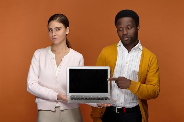 Stilvolles interracial-team von zwei kollegen, schwarzem mand und weißer frau, die eine drahtlose internetverbindung genießen, während sie einen tragbaren computer mit einem leeren schwarzen display mit copyspace für ihre informationen verwenden