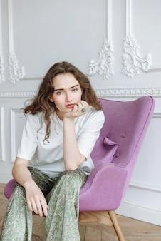 Stilvolles junges brünettes model sitzt auf einem stuhl im studio und schaut in die kamera