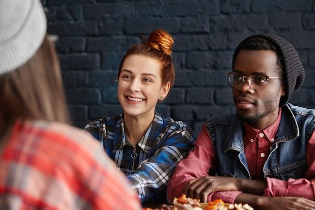 Stilvolles junges interracial paar, das mittagessen im restaurant hat