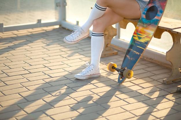 Stilvolles junges mädchen, das auf bushaltestelle mit ihrem longboard, hörender musik sitzt und auf bus wartet