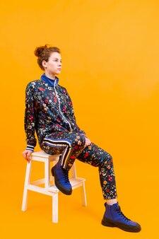 Stilvolles junges mädchen, das auf trittleiter über orange wand aufwirft