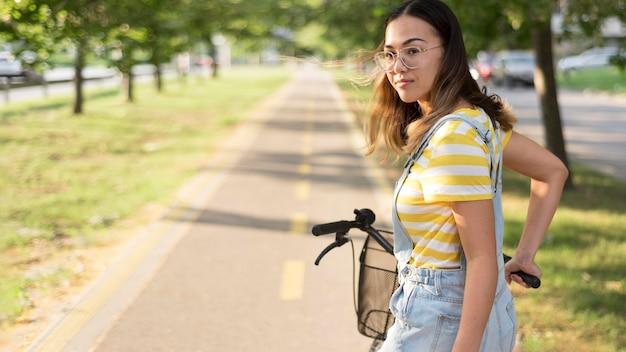 Stilvolles junges mädchen, das fahrrad reitet