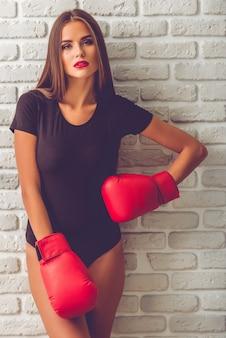 Stilvolles junges mädchen im schwarzen bodysuit und in den boxhandschuhen.
