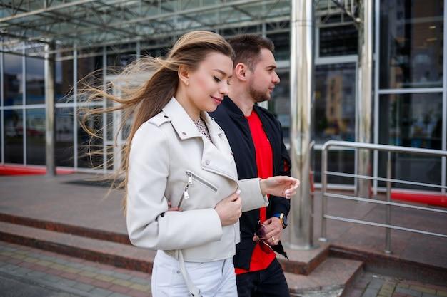 Stilvolles junges mädchen mit blonden haaren europäischen aussehens und einem mann in einer schwarzen jacke. urbaner spaziergang eines verliebten paares, moderne mode im lässigen stil. glückliches beziehungskonzept
