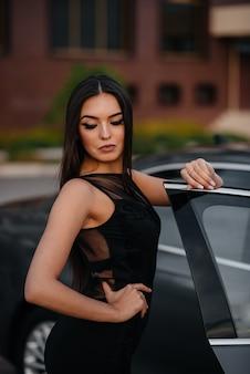 Stilvolles junges mädchen steht in der nähe des autos in einem schwarzen kleid.