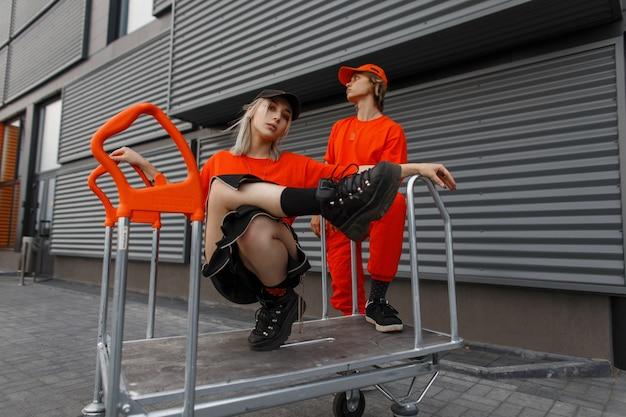 Stilvolles junges paar mit kappen in orange modischer kleidung mit turnschuhen, die auf einem wagen nahe der metallwand sitzen