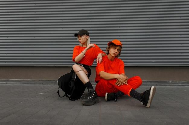 Stilvolles junges paar mit mützen in modischen orangefarbenen kleidern, die auf der straße nahe der grauen metallwand sitzend aufwerfen