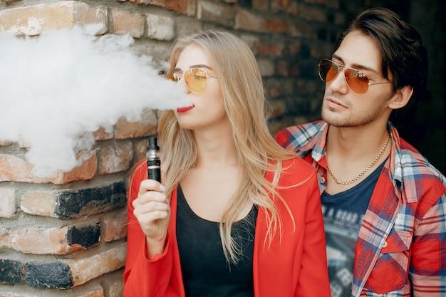 Stilvolles junges paar mit vape in einer stadt
