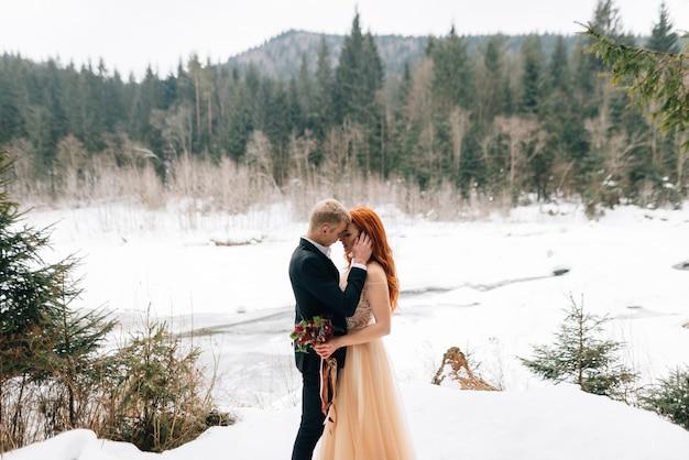 Stilvolles junges schönes paar, braut und bräutigam, winterschneelügen, hochzeit in der kalten jahreszeit