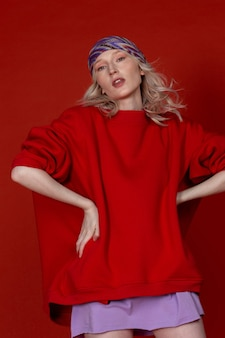 Stilvolles kaukasisches blondes mädchen in schickem sportoutfit, das auf dem roten hintergrund posiert