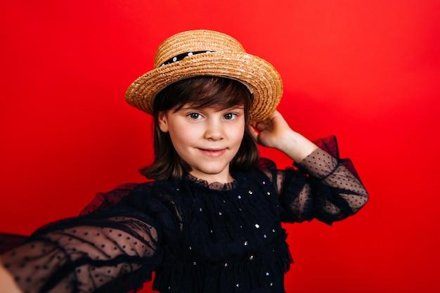 Stilvolles kind im strohhut, das selfie macht. süßes weibliches kind im schwarzen kleid.