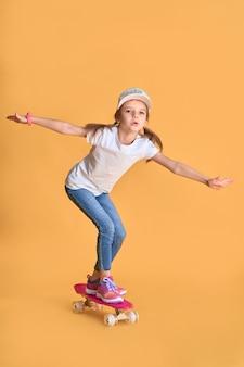 Stilvolles kindermädchen des kleinen mädchens in zufälligem mit skateboard über gelber wand