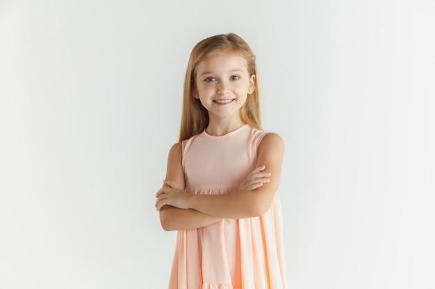 Stilvolles kleines lächelndes mädchen, das im kleid lokalisiert auf weißem studiohintergrund aufwirft. kaukasisches blondes weibliches modell. menschliche gefühle, gesichtsausdruck, kindheit. mit gekreuzten händen stehen.