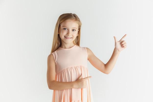 Stilvolles kleines lächelndes mädchen, das im kleid lokalisiert auf weißer wand aufwirft. kaukasisches blondes weibliches modell. menschliche gefühle, gesichtsausdruck, kindheit. zeigen auf eine leere leertaste.