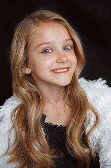 Stilvolles kleines lächelndes mädchen, das im weißen outfit lokalisiert auf schwarzer studiowand aufwirft