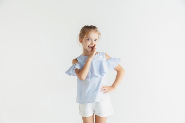 Stilvolles kleines lächelndes mädchen, das in der freizeitkleidung aufwirft